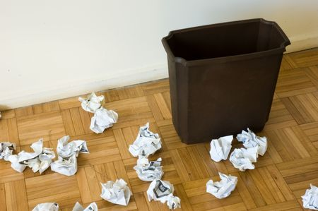 empty trashcan with a lots of papers around it Stock Photo