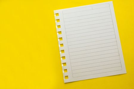 sheet from spiral notepad on yellow background photo