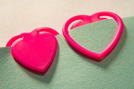 heart shape paper clips attached to blank paper note Stock Photo