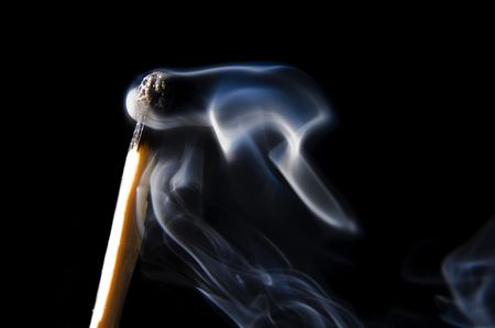 close up on matchstick with smoke on black background photo