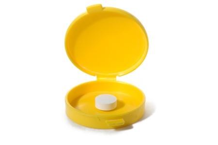 white pill in yellow pillbox