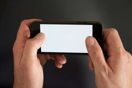 a man holds a black smartphone on black  photo
