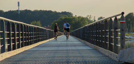 ramble: illustration of a couple that makes cycling on a bridge Stock Photo