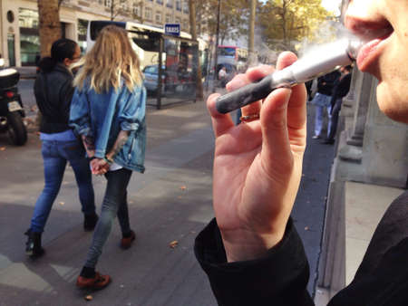 A woman smokes in the streets of Paris