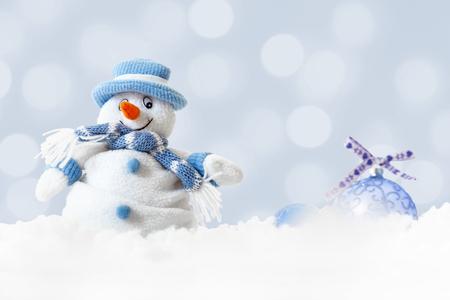 Weihnachtsglücklicher Schneemann, der blauen Hut und Schal mit Weihnachtsbällen auf abstraktem Lichthintergrund, weiße weiche Schneeflocken fallen auf Winterlandschaft, frohe Weihnachten und guten Rutsch ins Neue Jahr-Grußkarte trägt