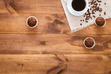 Cup of black coffee, muffins and coffe beans scattered on brown wooden table, cofee cafe cafeteria shop background, hot drink in mug with cakes morning breakfast menu, top close up view, copy space