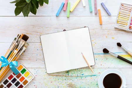 Colorful creative table with blank notebook for sketches and paints, pencil, paintbrushes set and cup of coffee on white wooden table, top view, copy space, flat lay style, drawing class education