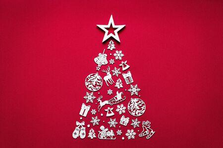 Weihnachtsbaum-Hintergrundkonzept verziert aus weißen Holzspielzeugdekorationen einzeln auf rotem Tisch flach, fröhlicher Weihnachtswinter minimale festliche Feierkomposition, Draufsicht oben, Kopierraum