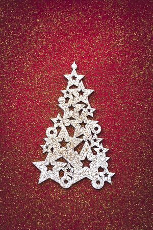 Merry christmas tree concept white 2020 happy new year wooden decoration top view isolated on red background table minimal flat lay with gold glitter, winter holiday party event card, vertical