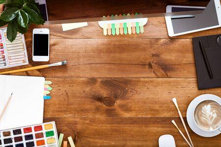 Modernes kreatives Design-Arbeitsplatzkonzept, Computermonitor und Farbstiftgeräte auf braunem Holztisch mit leerem Mock-up-Raum für Grafikdesignerarbeit, flache Lage, Draufsicht des Arbeitsbereichs Standard-Bild