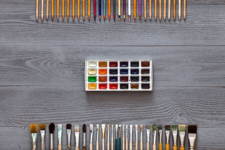 Art creative table background with watercolor paints palette paintbrushes pencils supplies tools on grey wooden desk, artist gray design blank workspace top view from above, flat lay, copy space Zdjęcie Seryjne