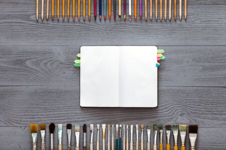 Creative art work table concept, mock up blank notebook sketchbook, paintbrushes and pencils set for creativity sketches on grey wooden background, top view from above, flat lay, copy space