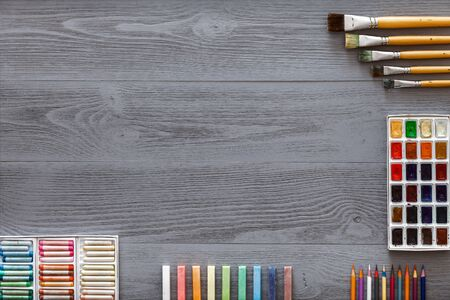 Art creative table background with watercolor paints palette paintbrushes pencils crayons supplies tools on grey wooden desk, artist gray design workspace top view from above, flat lay, copy space Zdjęcie Seryjne