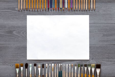 Creative table background with paintbrushes pencils and mockup paper for sketches supplies on grey wooden desk, art gray design workspace, teaching painting, top view from above, flat lay, copy space