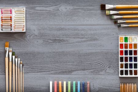 Art creative table background with watercolor paints palette paintbrushes pencils crayons supplies tools on grey wooden desk, artist gray design workspace top view from above, flat lay, copy space Imagens