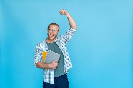Bearded happy excited student in glasses hold copybook win victory gesture