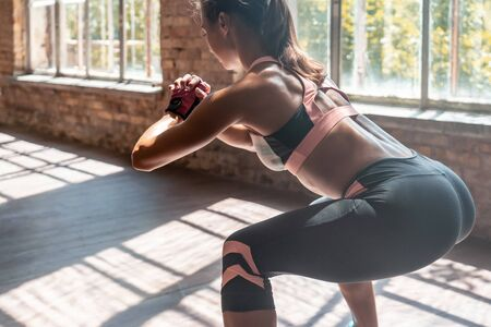 Closeup young sporty woman fitness trainer do squats healthy lifestyle.