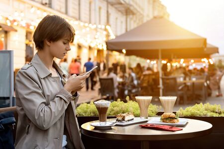 Millennial girl blogger taking food picture on phone sit in city cafe Stock Photo