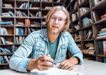 Male online tutor teacher looking at camera teaching student online.