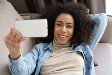 Relaxed african woman hold smartphone watching movie, making video call at home.