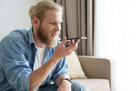 Young man using virtual digital voice assistant on mobile phone app.
