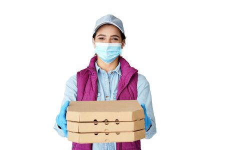 Hispanic woman courier wears mask gloves holding pizza boxes isolated on white. Foto de archivo