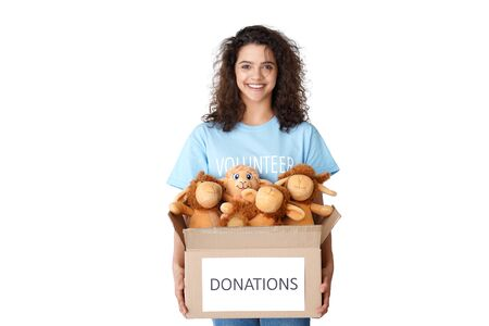 Smiling young hispanic girl volunteer holding donation box with toys.