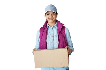 Smiling young hispanic woman courier holding delivery box isolated on white. Фото со стока