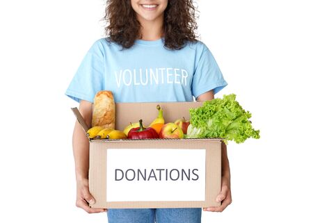 Smiling woman courier volunteer holding social food donations box close up. Imagens