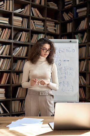 Hispanic woman teacher working in classroom with whiteboard and laptop. 免版税图像