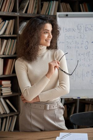 Happy confident hispanic young woman teacher looking away dreaming in classroom. 免版税图像