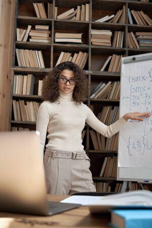 Young hispanic woman tutor teaching math class explaining remote course lesson.