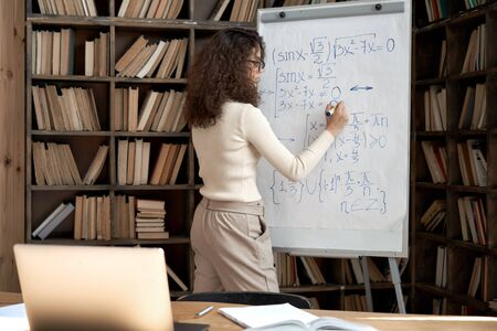 Female latin indian math school teacher student writing equation on whiteboard. 免版税图像