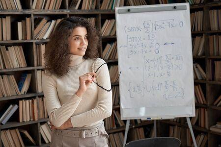 Smiling hispanic young woman math teacher looking away dreaming in classroom.