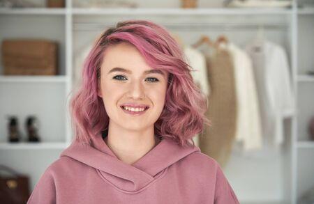 Happy hipster gen z teen girl fashion designer with pink hair headshot portrait.