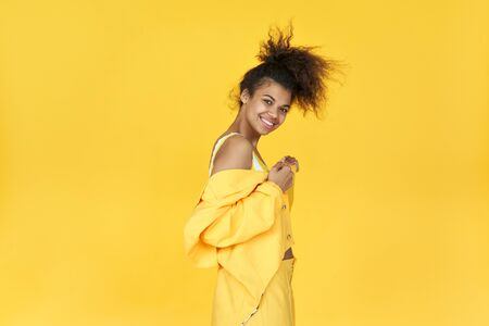Happy afro girl wear stylish yellow cloth dance isolated on yellow background.