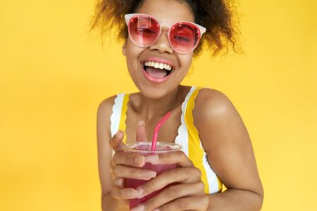 Excited african girl wear sunglasses hold drink look at camera in yellow studio.