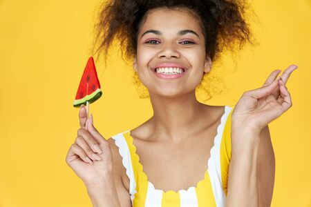 Happy african gen z teen girl hold candy isolated on yellow summer background. Standard-Bild - 147820250