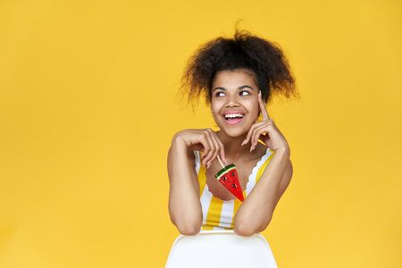 Happy african teen girl hold candy sit on chair isolated on yellow background. Standard-Bild