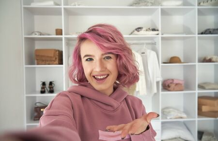 Happy hipster gen z teen girl fashion blogger with pink hair recording vlog.