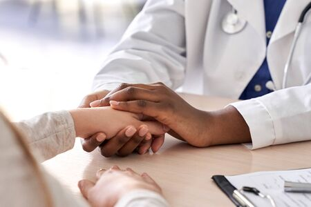 African doctor hold hand of caucasian patient give comfort, compassion, closeup.