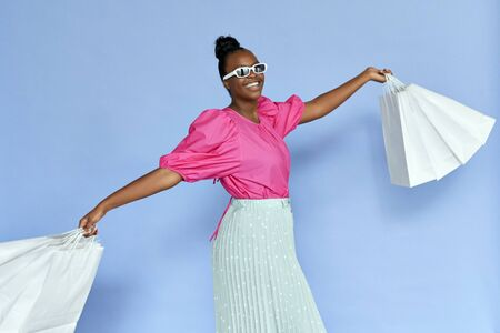 Fashion african woman wear sunglasses holding shopping bags isolated on violet.
