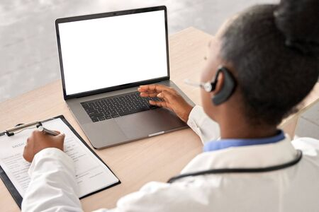 African doctor talk to patient by online webcam video call on laptop screen.