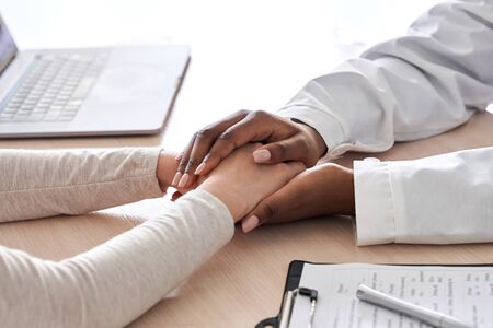 African female doctor holding hand supporting caucasian patient, close up view. Standard-Bild