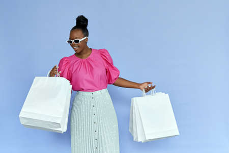 Excited african woman looking inside shopping bags isolated on violet. Standard-Bild