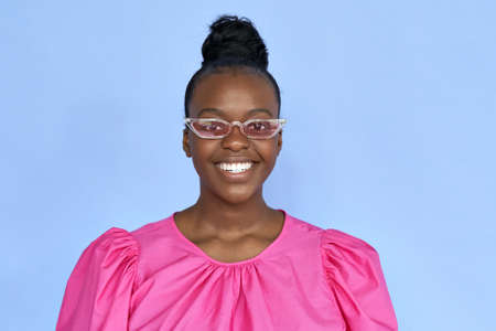 Happy african woman wearing trendy cloth and pink sunglasses isolated on lilac. Standard-Bild