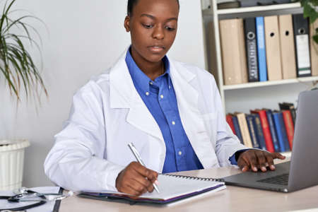 African american doctor writing medical record in notebook using laptop at desk. Standard-Bild