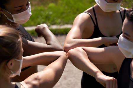 Diverse multiracial fit girls friends wear face masks give elbow bump. Standard-Bild
