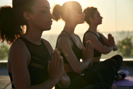 Calm serene african american woman meditating at outdoor group yoga class. Standard-Bild