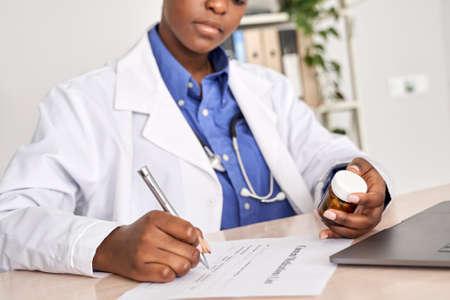 African american doctor writing prescription holding pills bottle sit at desk.